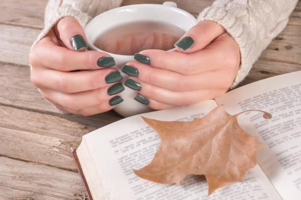 frau die hände im pullover mit olive farbe maniküre hält tasse tee und offenes buch - herbst nagellack stock-fotos und bilder