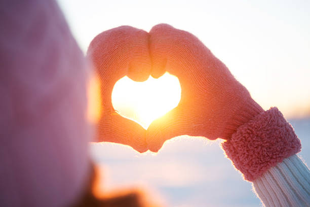 Woman hands in winter gloves Heart symbol stock photo