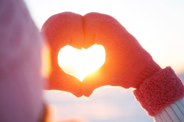 woman hands in winter gloves heart symbol - new year day stock photos and pictures