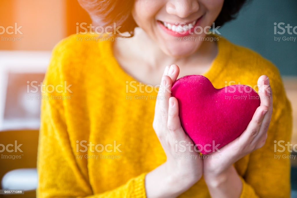 Woman  hands in yellow sweater holding pink heart.