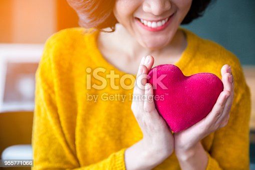 istock Woman  hands in yellow sweater holding pink heart. 955771066