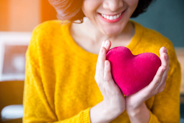 woman  hands in yellow sweater holding pink heart. - health and beauty stock photos and pictures