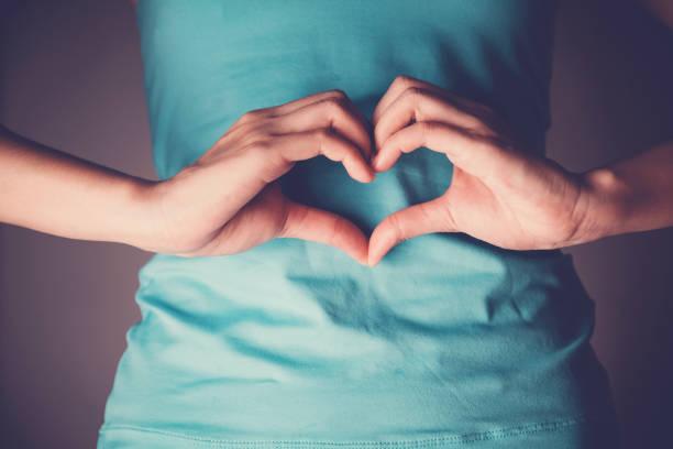 mãos da mulher que fazem uma forma do coração em seu estômago, degestion saudável das entranhas, probióticos para a saúde do intestino - abdome - fotografias e filmes do acervo