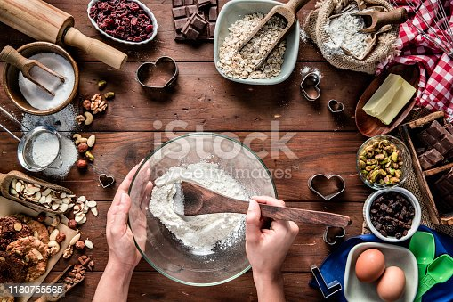 Woman hands making chocolate and nuts cookies on rustic table with digital food weight scale.  Christmas themes.