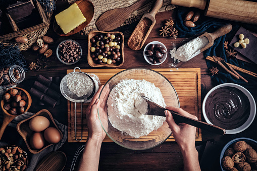 Woman hands making chocolate mousse and cookies on a wooden table in a rustic kitchen