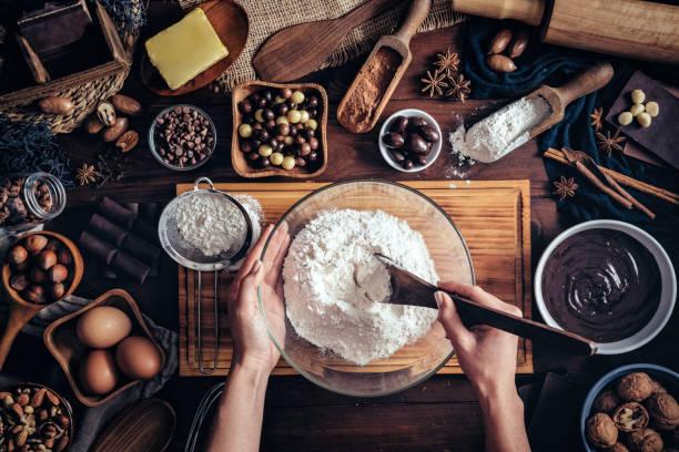 mãos da mulher que fazem o mousse e os bolinhos de chocolate em uma tabela de madeira em uma cozinha rústica - receita - fotografias e filmes do acervo