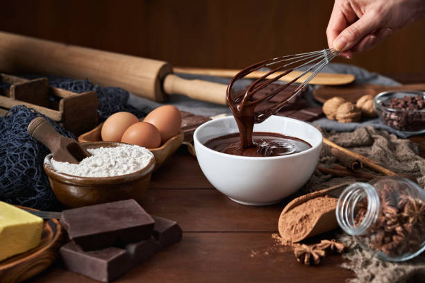 Woman hands making chocolate mousse and cookies on a wooden table in a rustic kitchen stock photo