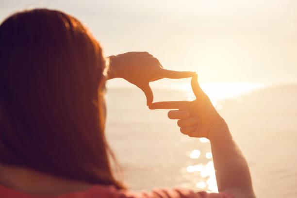 Frau die Hände machen Frame Geste mit Sonnenaufgang, vorstellen, Zukunft – Foto
