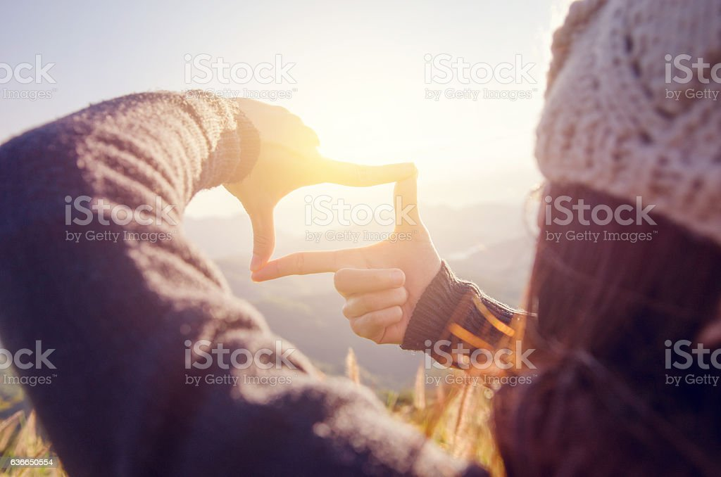 Woman hands making frame gesture with sunrise. stock photo