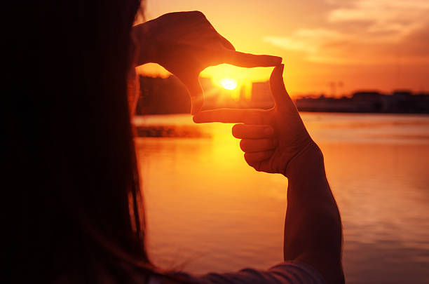 Woman hands making frame gesture with sunset. - Photo