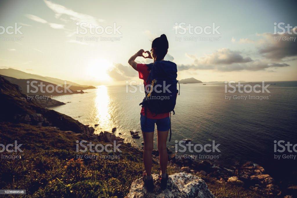 Woman hands making heart shape in sky stock photo