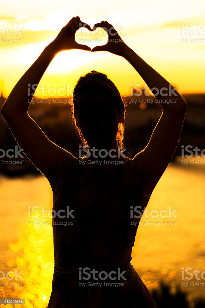 Woman hands making heart shape with background of Sunset sky stock photo