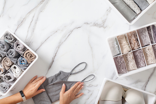 Woman hands neatly folding underwears and sorting in drawer organizers on white marble background