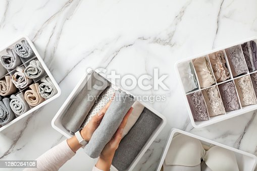 Woman hands neatly folding underwears and sorting in drawer organizers on white marble background. Closet tidying and decluttering concept. Copyspace. Hypoallergenic fabric. Organic cotton.