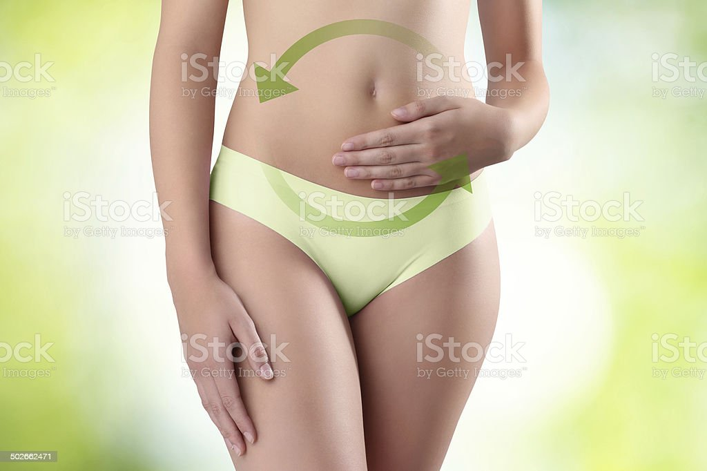 woman hands on belly with green arrow stock photo