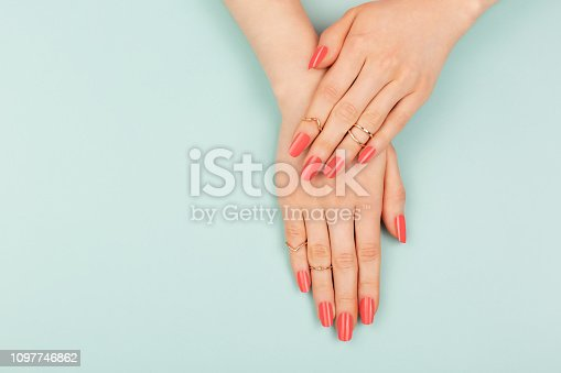 Manicure in trendy coral color. Woman hands on blue background. Color of 2019 year concept. Summer vibes. Copy space for your text.