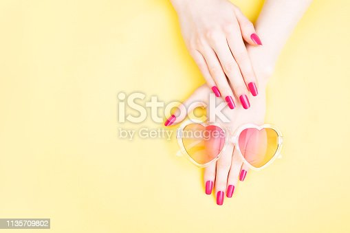 Summer manicure background. Beautiful female hands with perfect vibrant nails on yellow background. Heart shape sunglasses. Hands and nails care concept. Flat-lay, top view. Copy space.
