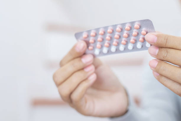 Woman hands opening birth control pills in hand. Eating Contraceptive Pill. Woman hands opening birth control pills in hand. Eating Contraceptive Pill. contraceptive stock pictures, royalty-free photos & images