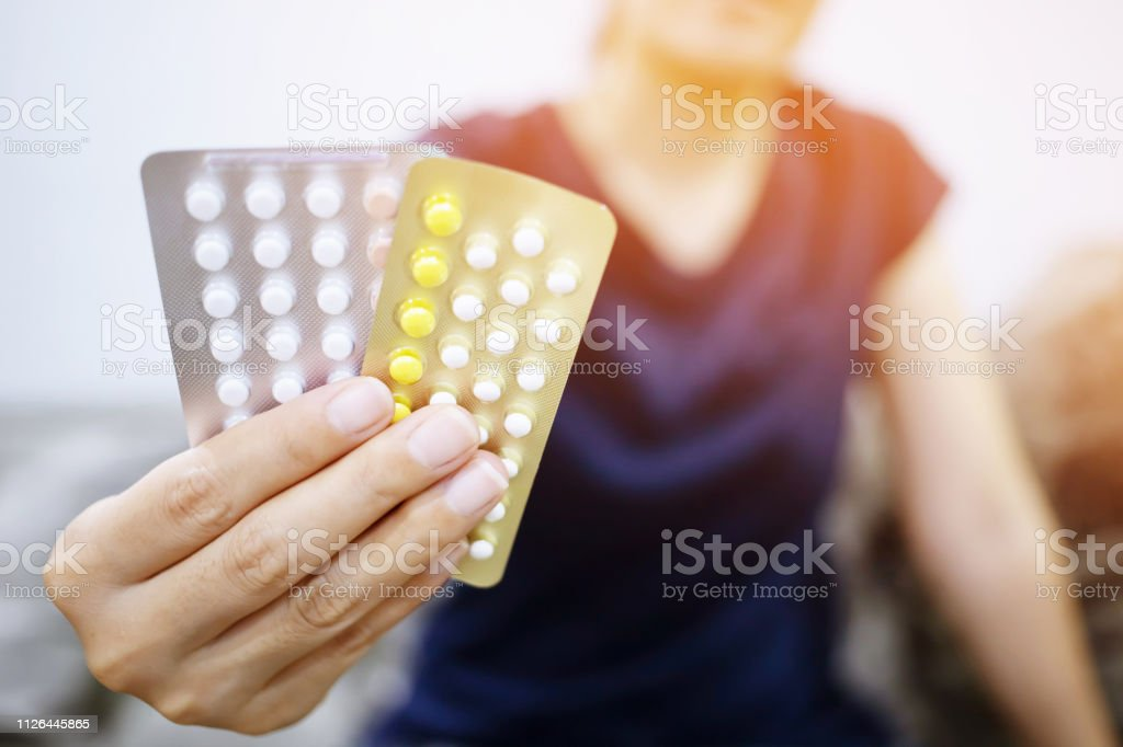 Woman hands opening birth control pills in hand on the bed in the...