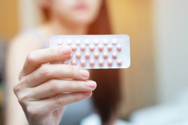 woman hands opening birth control pills in hand on the bed in the bedroom. eating contraceptive pill. - birth control pill stock photos and pictures