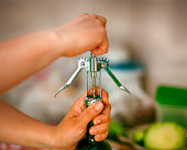 Woman hands opening wine bottle with corkscrew. Close up