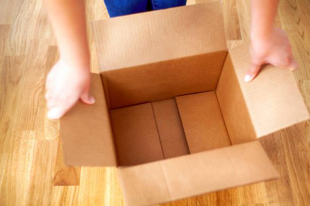 woman hands opens empty cardboard box. - puste pudełko zdjęcia i obrazy z banku zdjęć