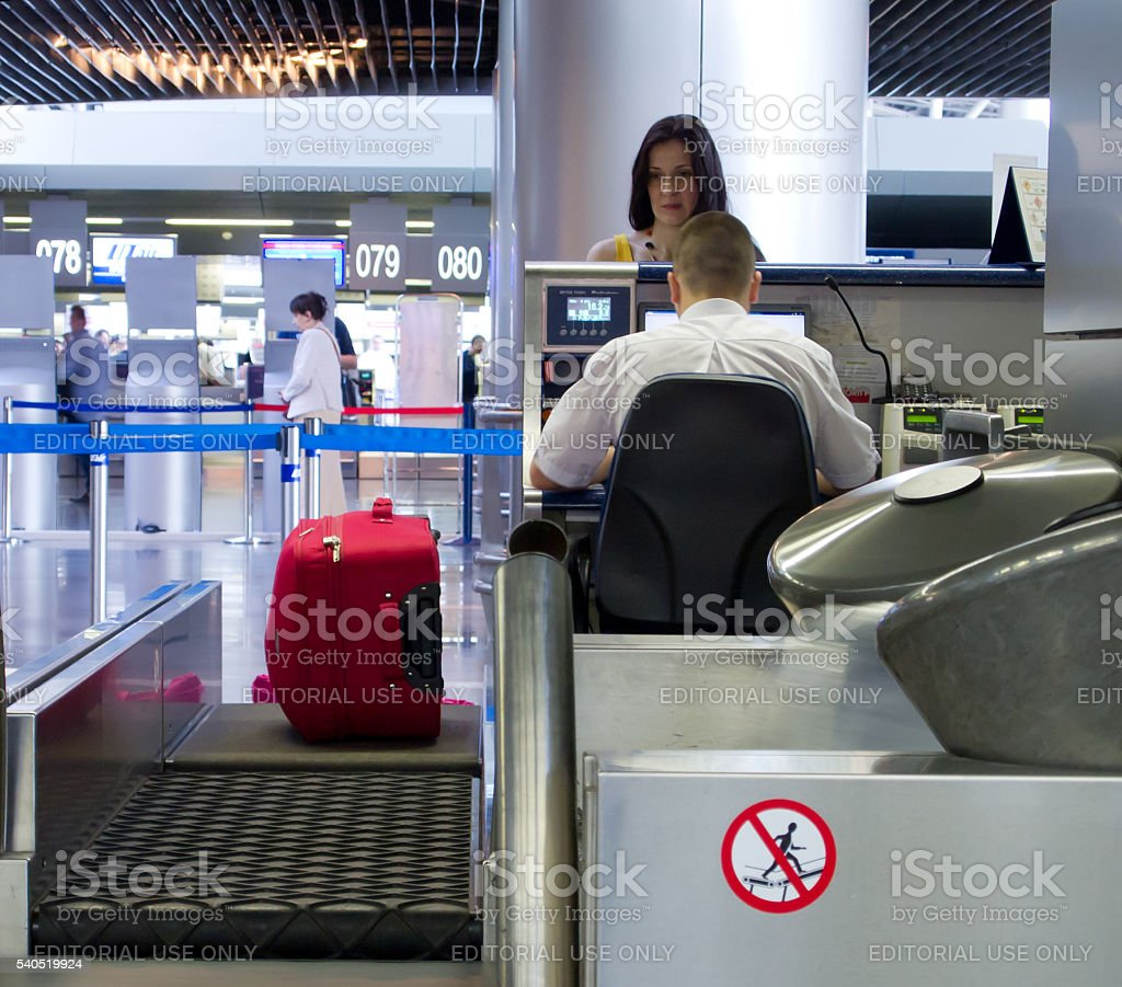 Woman hands over the luggage at the front desk stock photo