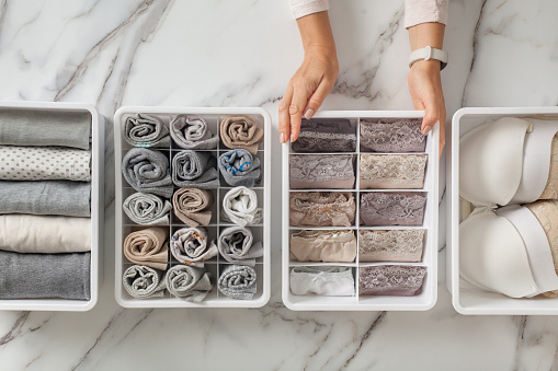Woman hands placing organizer drawer divider with full of folded underwears and socks