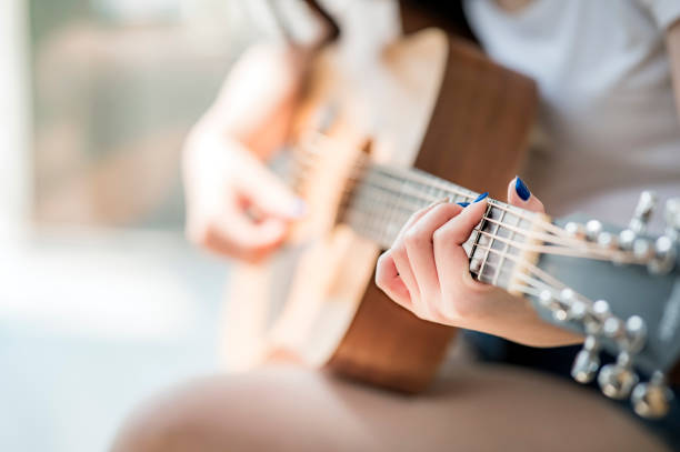 woman hands playing acoustic guitar stock photo