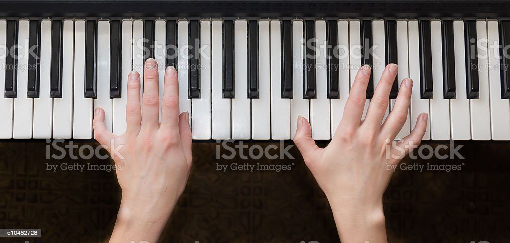 Woman hands playing piano music. stock photo