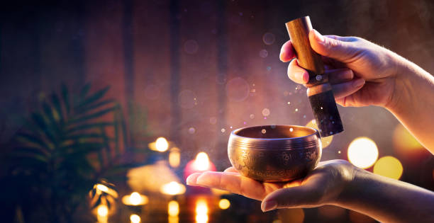 Woman Hands Playing Tibetan Singing Bowl - Translation of mantras : transform your impure body, speech, and mind into the pure exalted body, speech, and mind of a Buddha stock photo