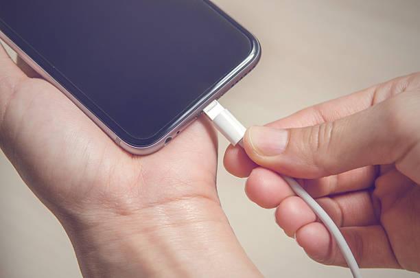 frau hände mit ladegerät anschluss in ein smart phone - aufladen stock-fotos und bilder
