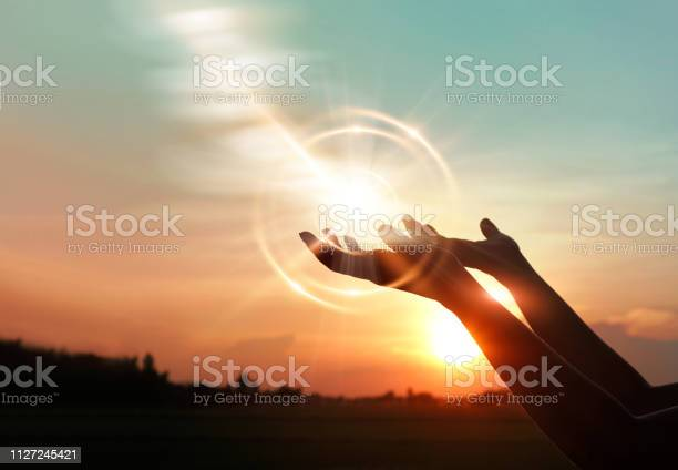 Photo of Woman hands praying for blessing from god on sunset background