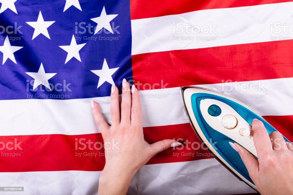 Woman hands pressing American Flag with an iron. Visual concept of preparation for Independence Day. Fourth of July patriotic consept stock photo