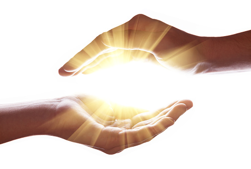 Woman hands protecting and containing bright, glowing, radiant, shining light.