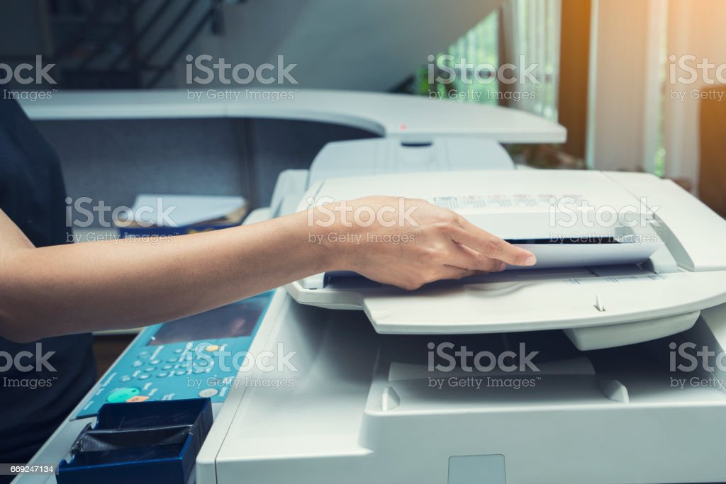 woman hands putting a sheet of paper into a copying device stock photo