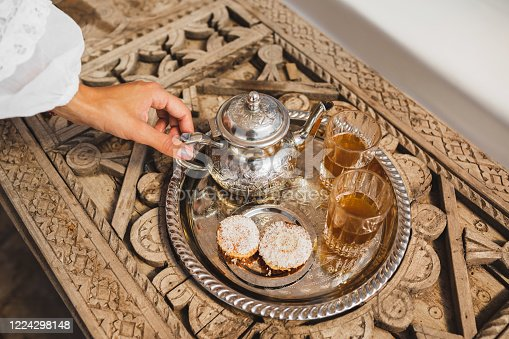 Woman hands serving traditional moroccan mint tea ceremony with cookies and vintage silver teapot. Hospitality and service in Morocco, Marrakech.