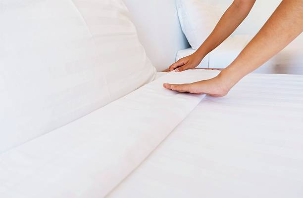 woman hands set up white bed sheet in hotel room stock photo