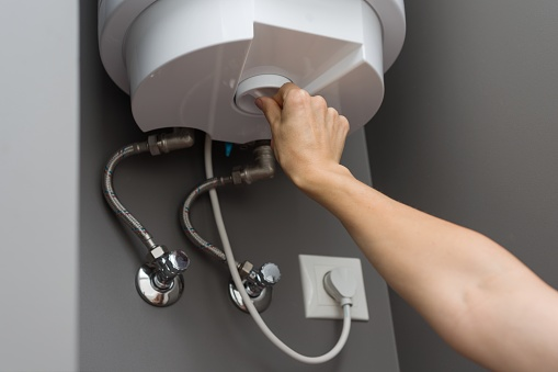istock Woman hands setting temperature of water in heater electric boiler. Interior details close-up. 996279800