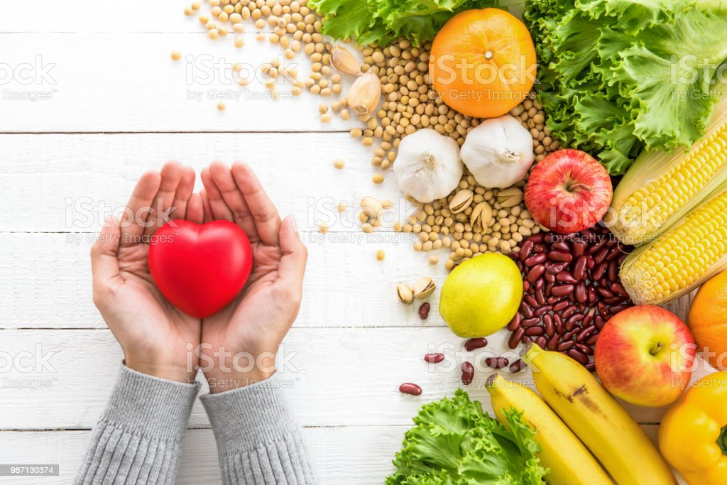 Woman hands showing red heart ball with healthy food aside stock photo