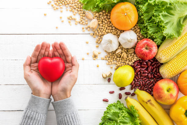 Woman hands showing red heart ball with healthy food aside Woman hands holding red heart shape ball with various kinds of colorful healthy medicinal fruits, vegetables and nuts aside on white wood table, top view cholesterol stock pictures, royalty-free photos & images