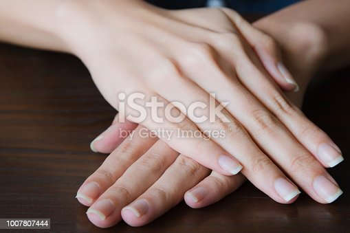 istock Woman hands showing with beautiful manicure on wooden background. 1007807444
