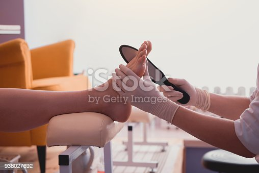 938027870 istock photo Woman hands taking care of girl leg 938027692