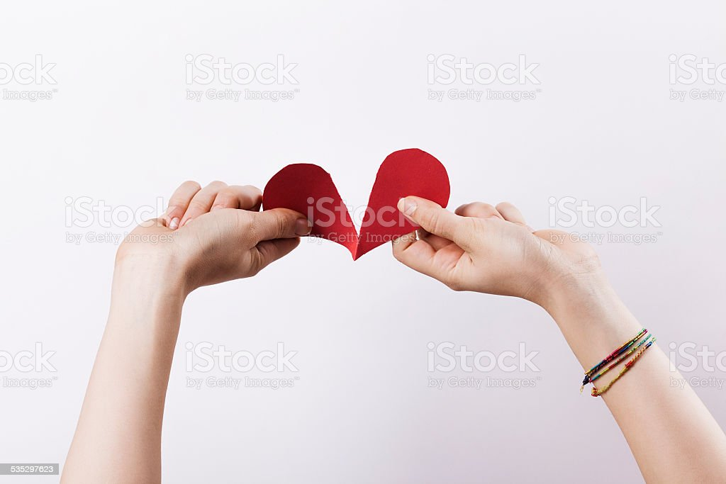 Woman hands tearing paper heart stock photo