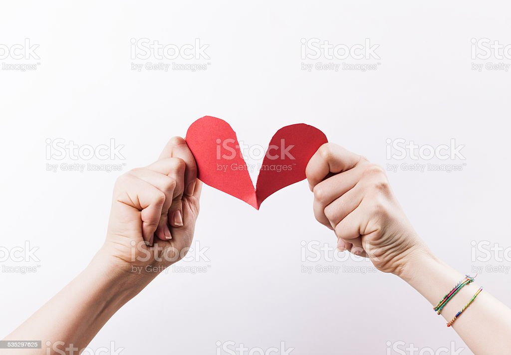 Woman hands tearing red paper heart stock photo