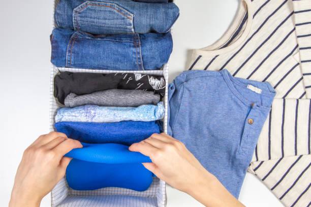 Frau Hände aufräumen Kinderkleidung im Korb. Vertikale Aufbewahrung von Kleidung, Aufräumen, Raumreinigungskonzept – Foto