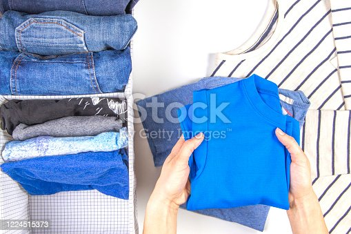 1146468292 istock photo Woman hands tidying up kids clothes in basket. Vertical storage of clothing, tidying up, room cleaning concept 1224515373