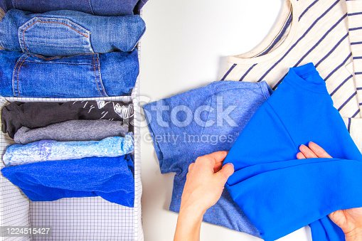 1146468292 istock photo Woman hands tidying up kids clothes in basket. Vertical storage of clothing, tidying up, room cleaning concept 1224515427