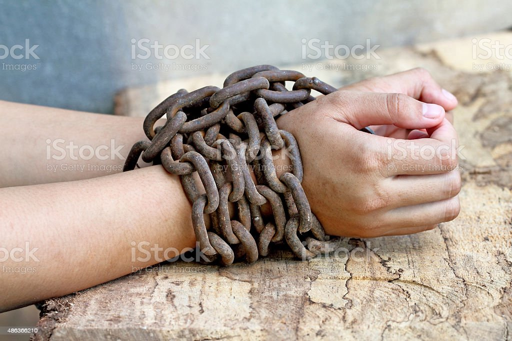 woman hands tied up with chain stock photo