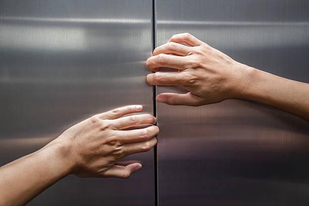 woman hands try to stop doors of the closed elevator - claustrofobie stockfoto's en -beelden
